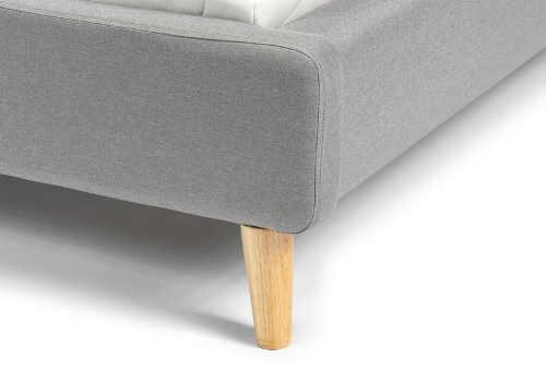 Šedá čalouněná postel s dřevěnýma nožkama