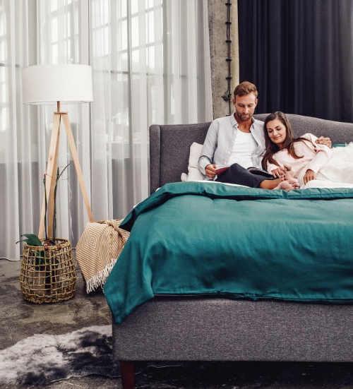 Šedá manželská postel s vysokým polstrovaným čelem
