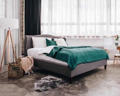 Šedá polstrovaná postel