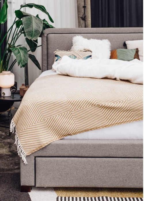 Šedá čalouněná postel s vysokým čelem