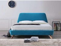 Čalouněná dvoulůžková postel v tyrkysovém provedení